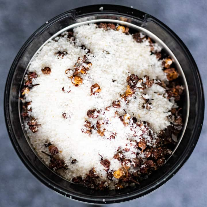 Overhead shot of toasted szechuan peppercorns and salt in a spice grinder.