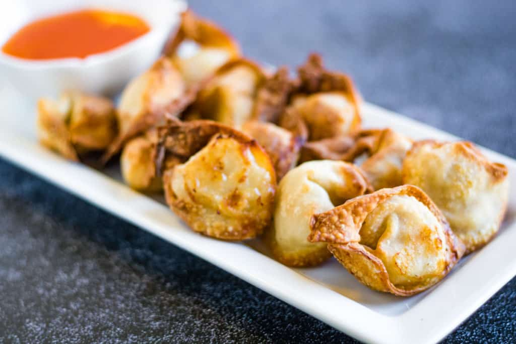 Low angle shot of air fryer wontons on a rectangular white plate with a small bowl of dipping sauce