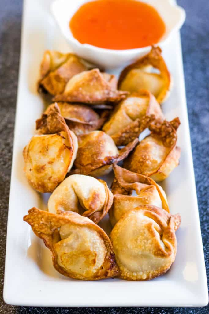 Low angle shot of the cooked wontons on a rectangular white plate with chili sauce in a dipping bowl.