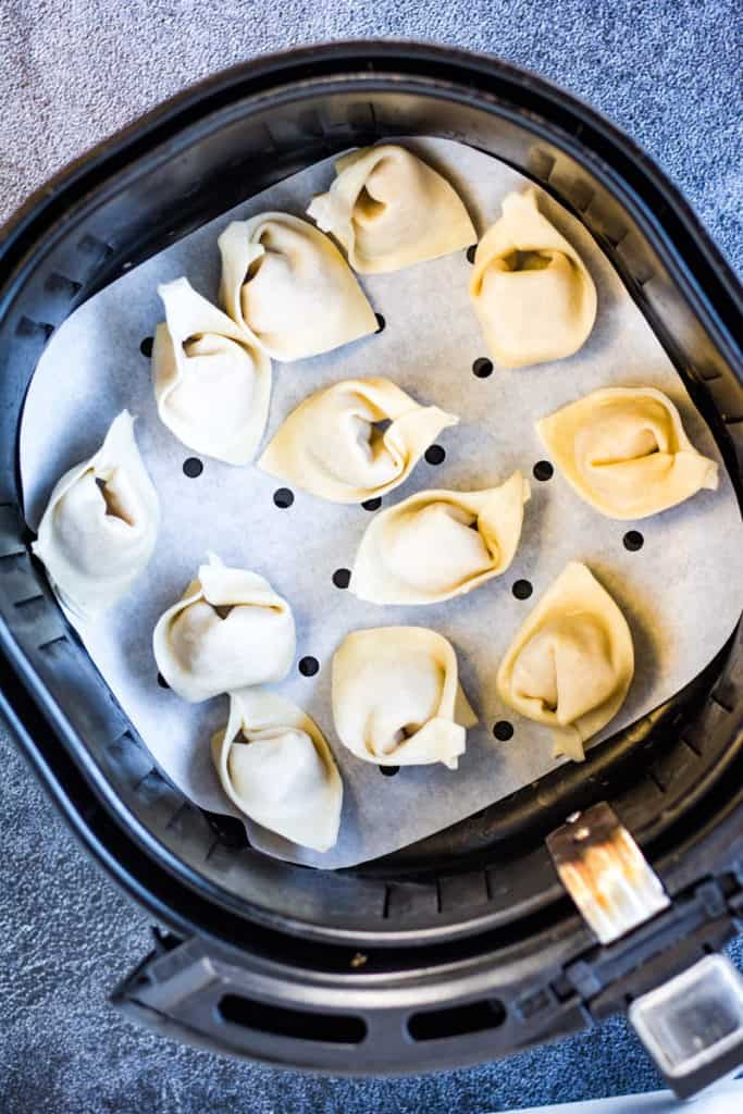 Overhead shot of the uncooked wontons in the air fryer basket