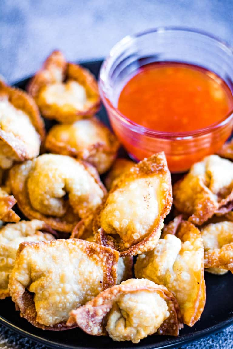 Low angle shot of fried wontons with dipping sauce.