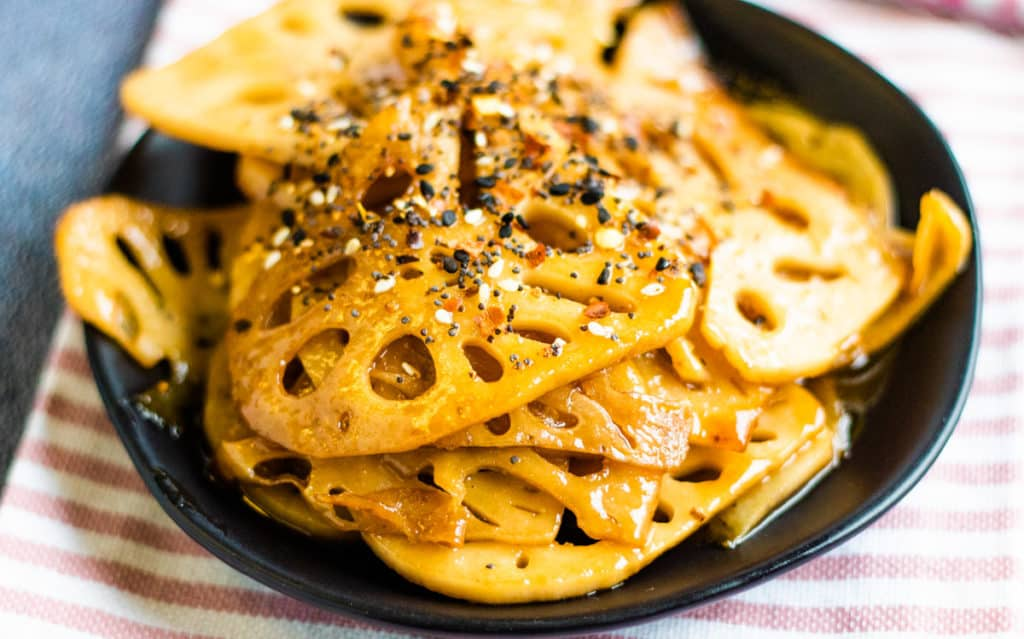 A low-angled shot of a pile of stir-fried lotus root on a black plate.