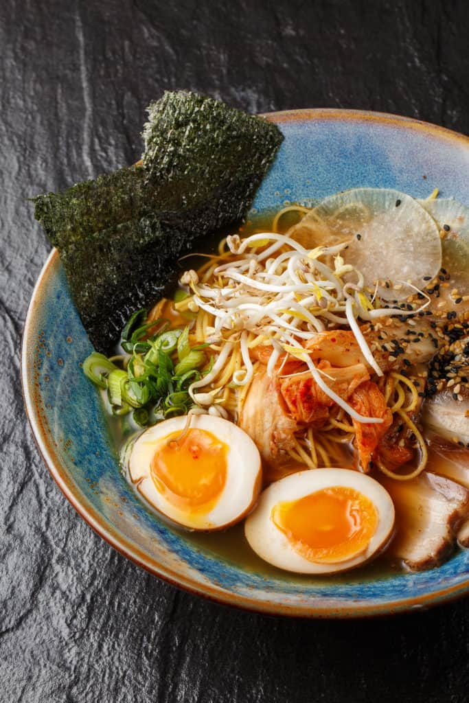 A bowl of ramen with 2 halves of soy sauce marinated egg on top.