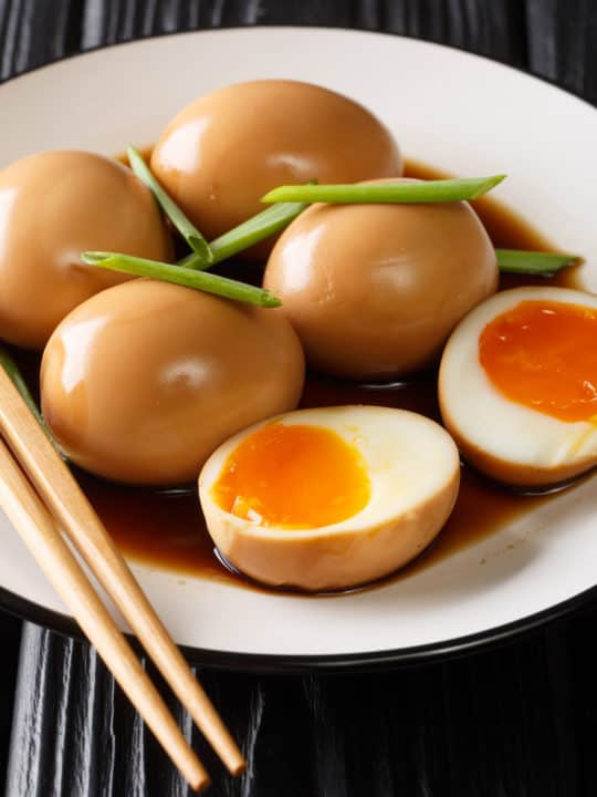 A low angle shot of soy sauce eggs on a white plate.