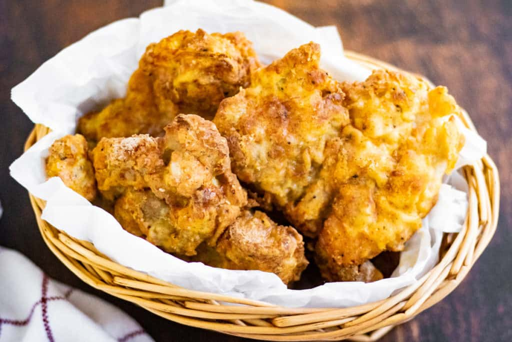 Air fryer fried chicken thighs in a basket lined with parchment paper.