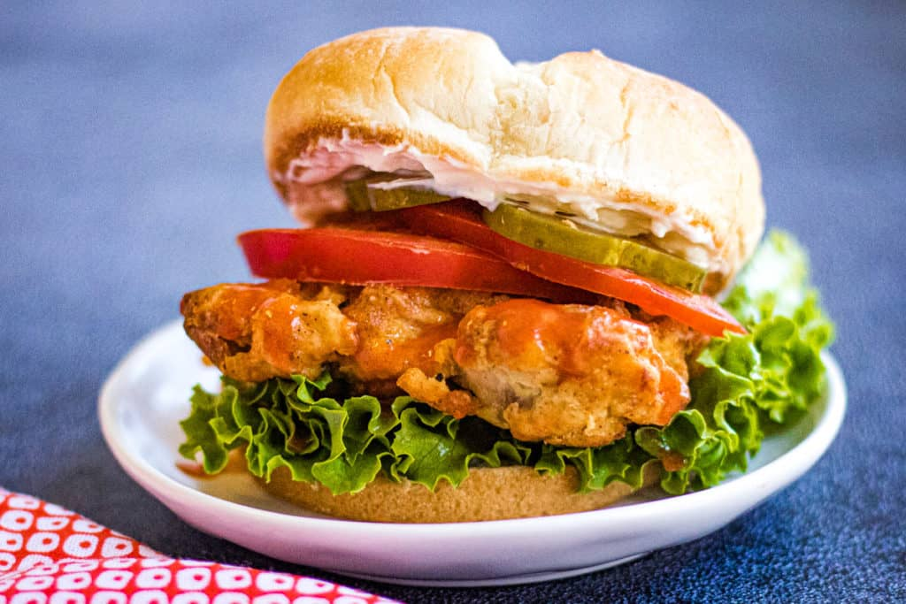 Low angle shot of an air fryer chicken sandwich on a white plate.
