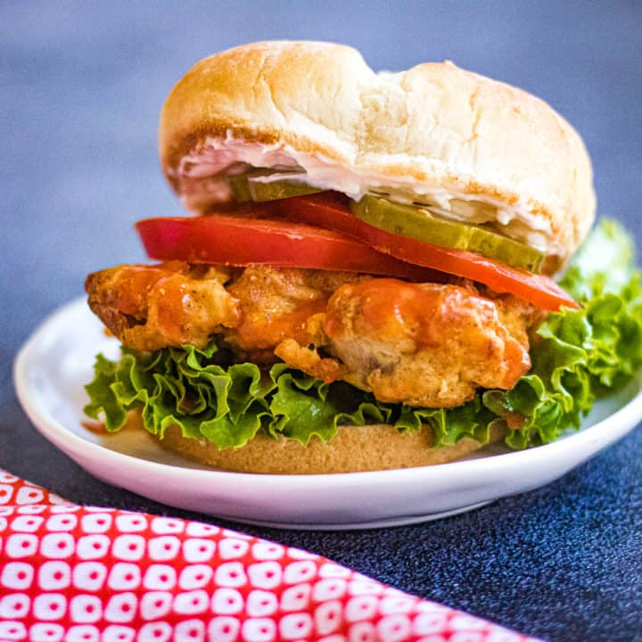Low angled shot of an air fryer fried chicken sandwich on a bun with lettuce, tomato, pickles, and mayo
