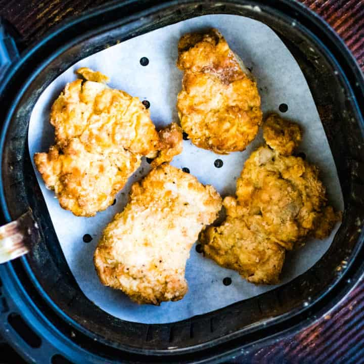Overhead shot of air fried chicken in the air fryer basket.