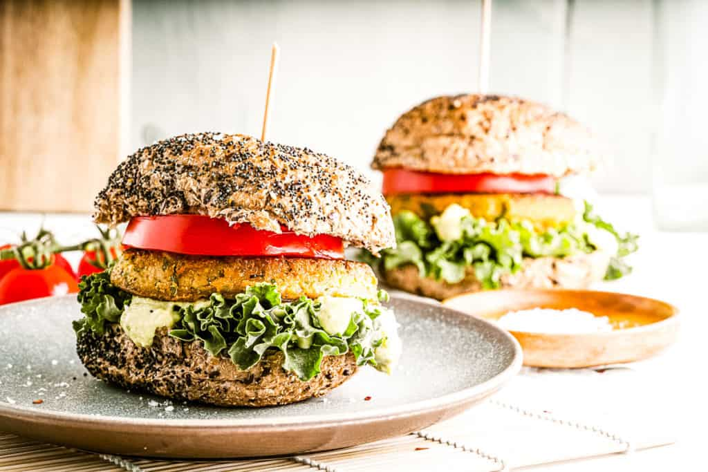 Low angle shot of 2 chickpea burgers on seeded buns with all the fixings.