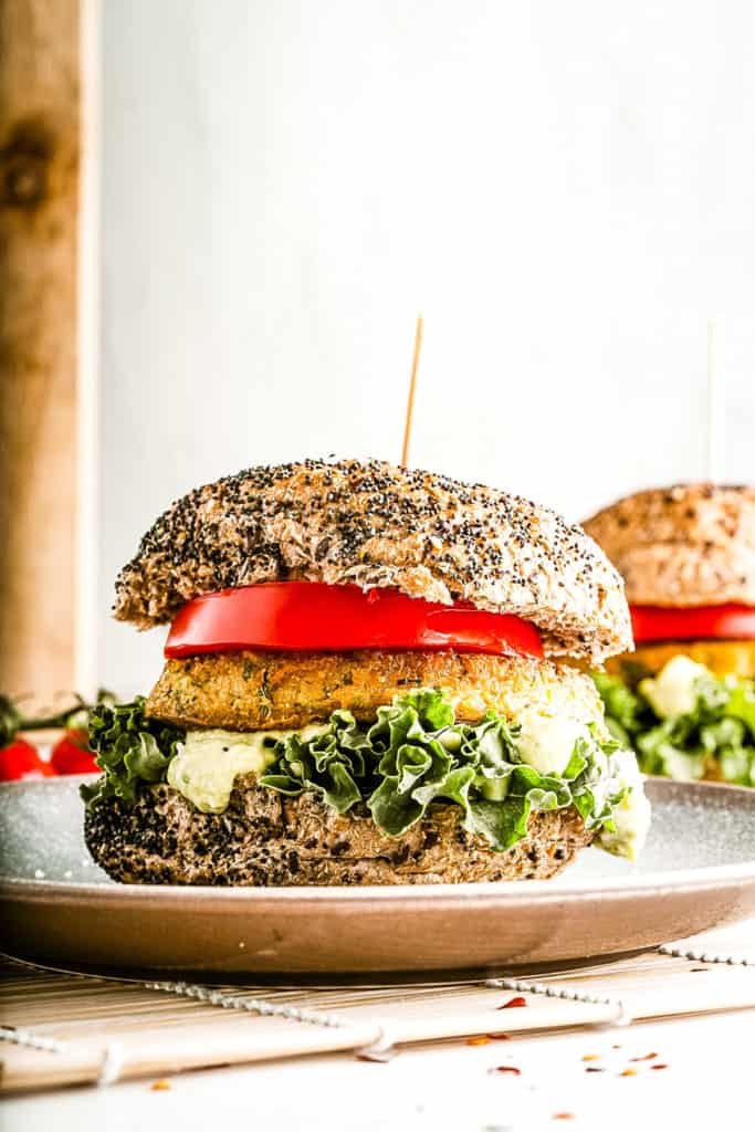 Low angle shot of a chickpea burger on seeded bun with all the fixings.