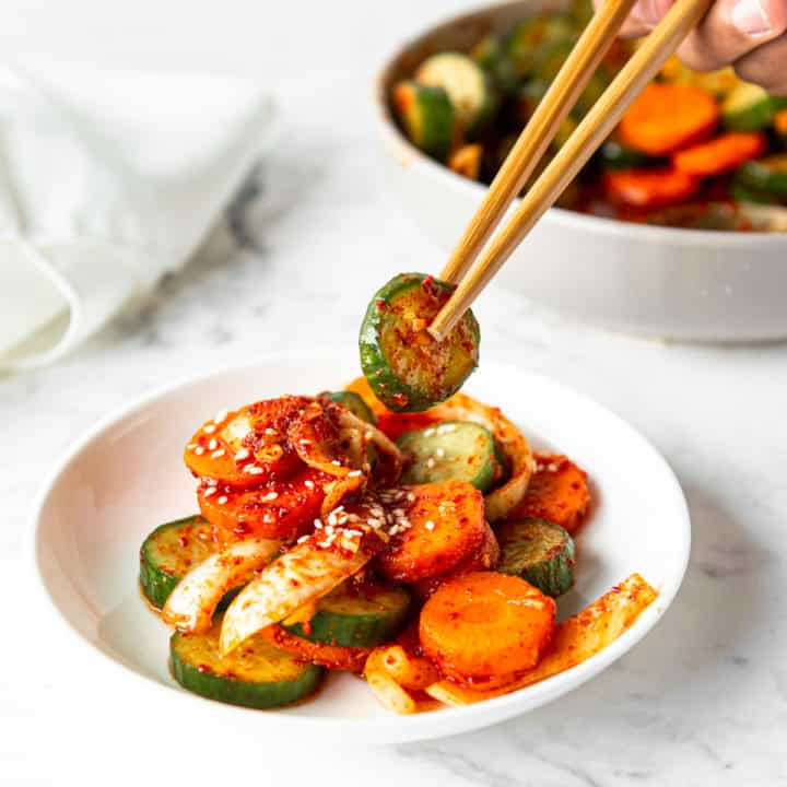 Low angle shot of a plate of cucumber kimchi with a hand lifting a cucumber slice with a pair of wooden chopsticks.