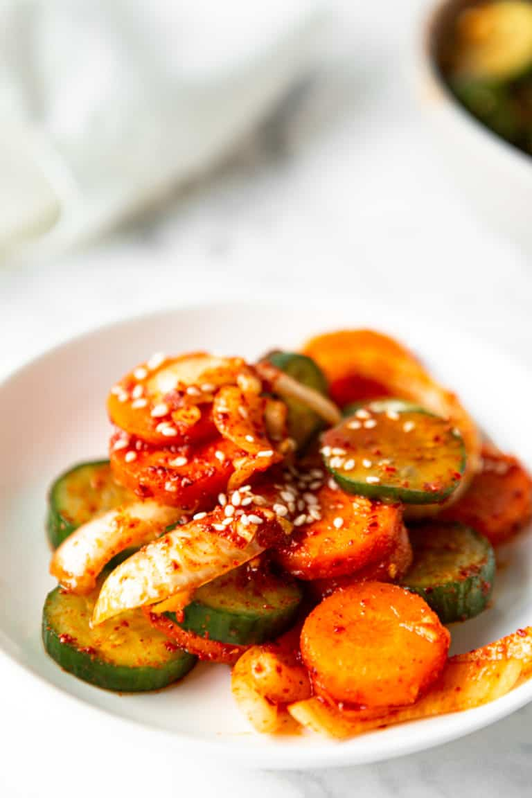 low angle shot of a white plate with cucumber kimchi on top