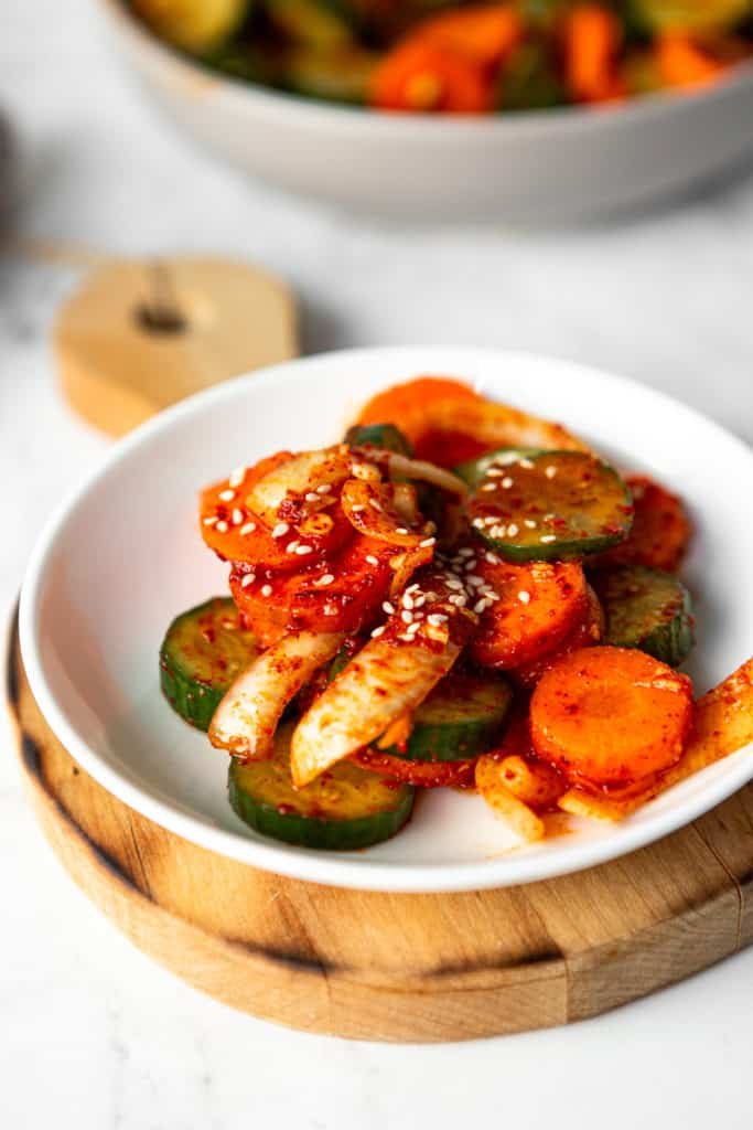 Low angle shot of a plate of cucumber kimchi.