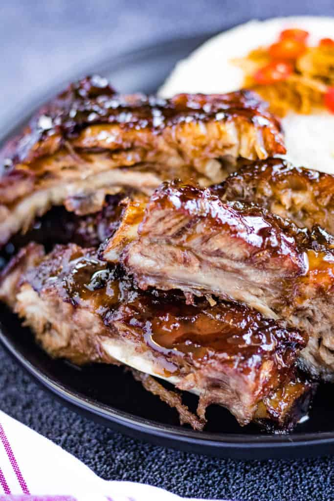 A low angled shot of the cooked ribs on a black plate with rice in the background.