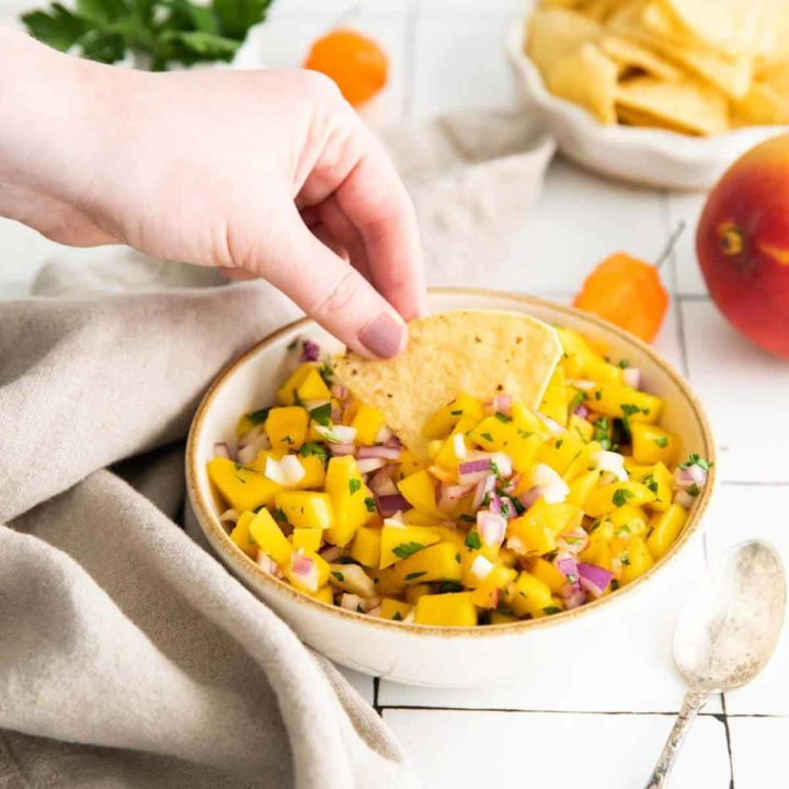 Low angle shot of a bowl of mango habanero salsa with a hand dipping a tortilla chip into the bowl.