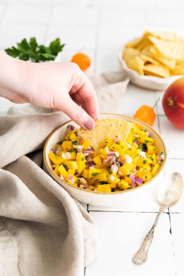 Low angle shot of mango salsa with a hand dipping a tortilla chip into the salsa.