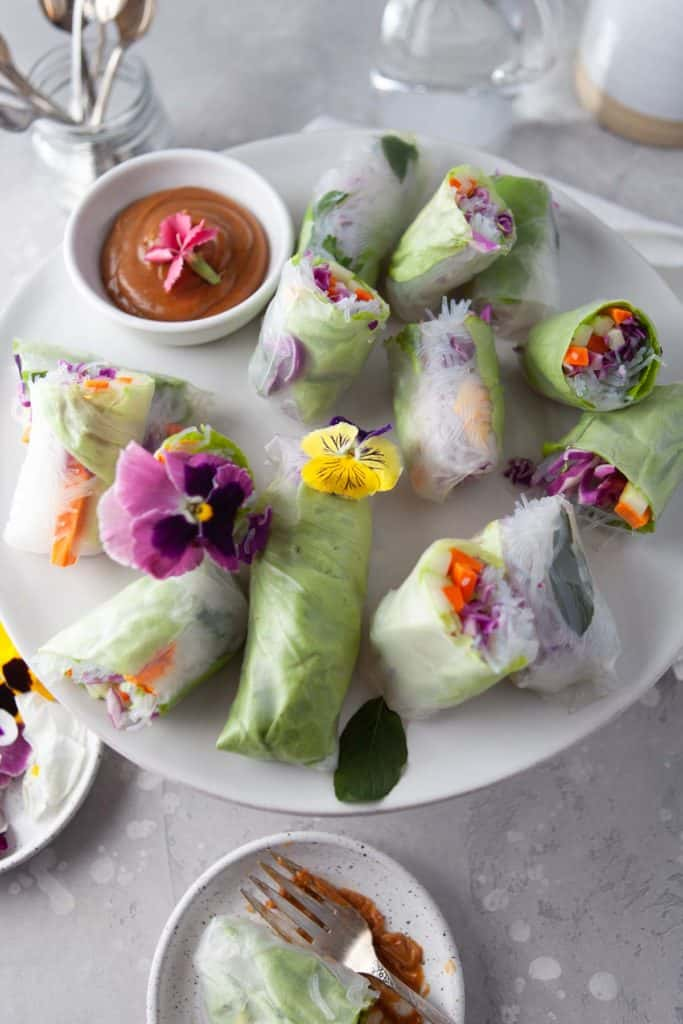A photograph of several fresh summer rolls on a platter with peanut sauce.