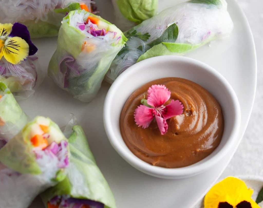 Low angle shot of a bowl of vietnamese peanut sauce with fresh rolls in the background.