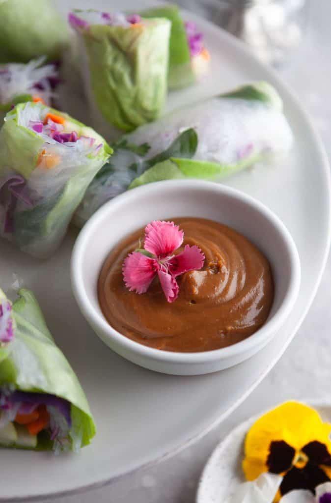 Shot of a bowl of Vietnamese peanut sauce on a platter with fresh summer rolls.