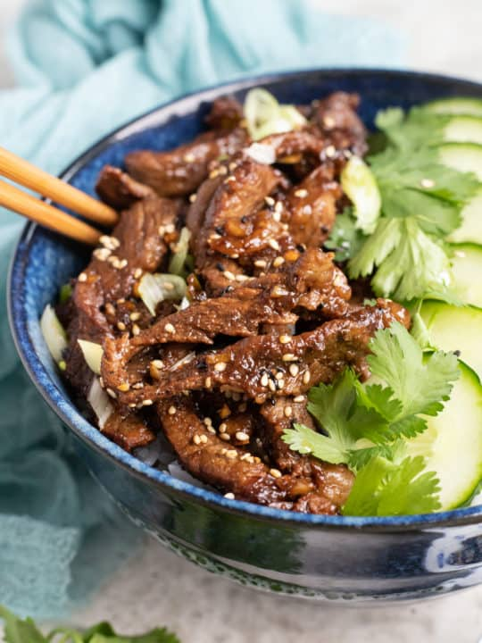 low angle shot of a blue bowl with Korean beef bulgogi over rice with sliced cucumbers, shredded carrots, and cilantro.