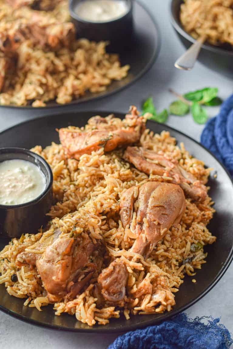 Low angle shot of chicken biryani on black serving plates.