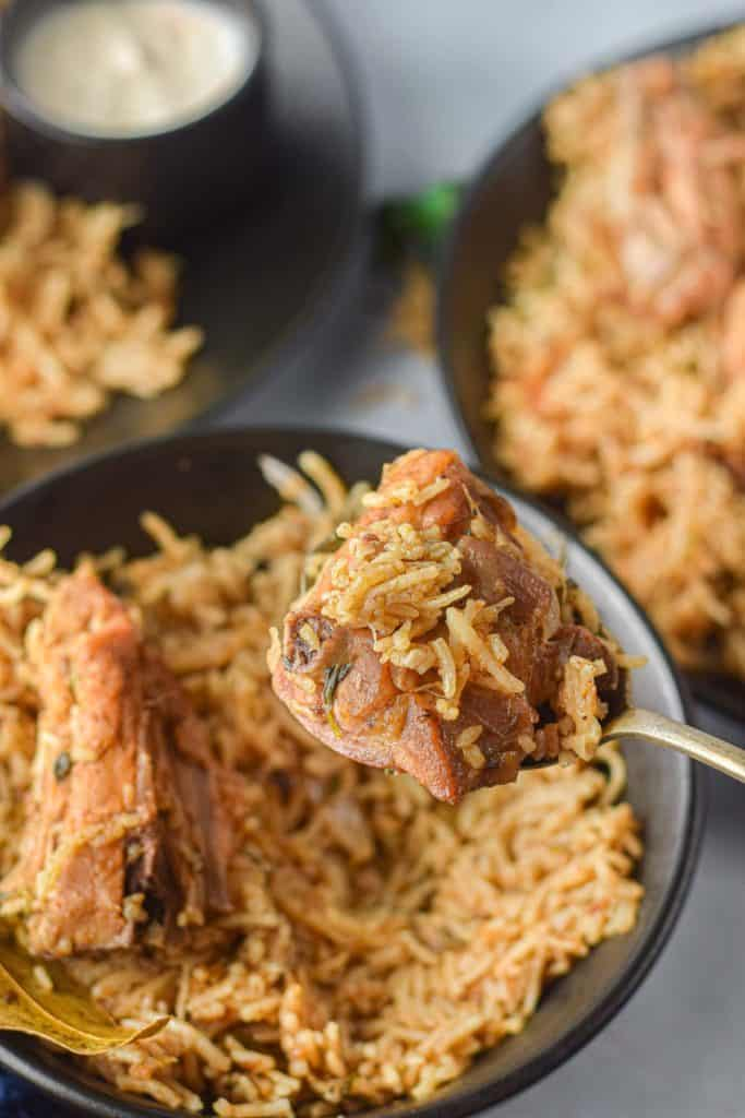 low angle shot of the cooked biryani with a forkful in the foreground