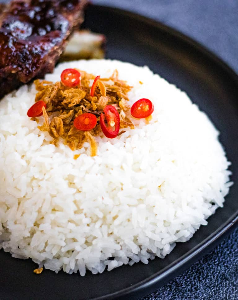 low angle shot of a mound of coconut rice garnished with fried shallots and sliced red chiles