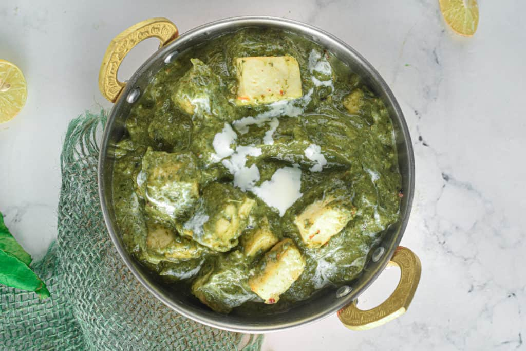 Overhead shot of a metal bowl filled with Instant Pot Palak Paneer