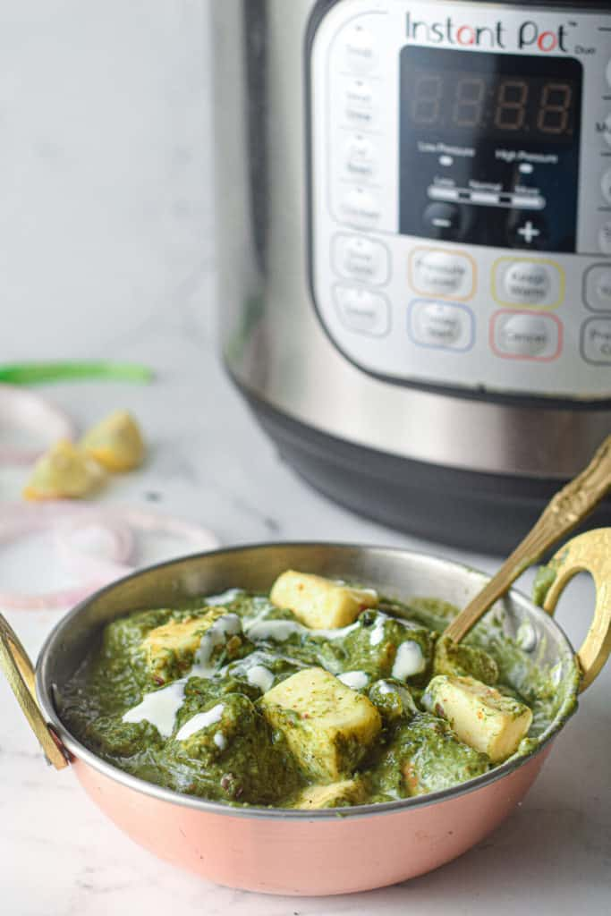 low angle shot of a bowl of palak paneer in front of an Instant Pot