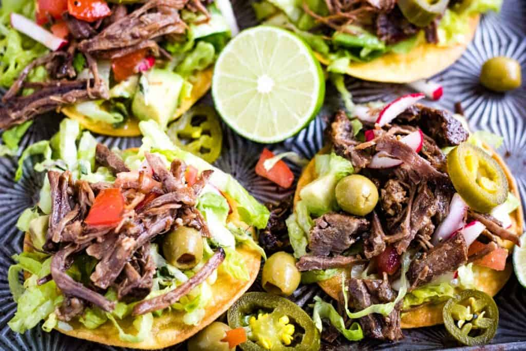 Low angle shot of salpicon de res or Mexican shredded beef salad on tostada shells.