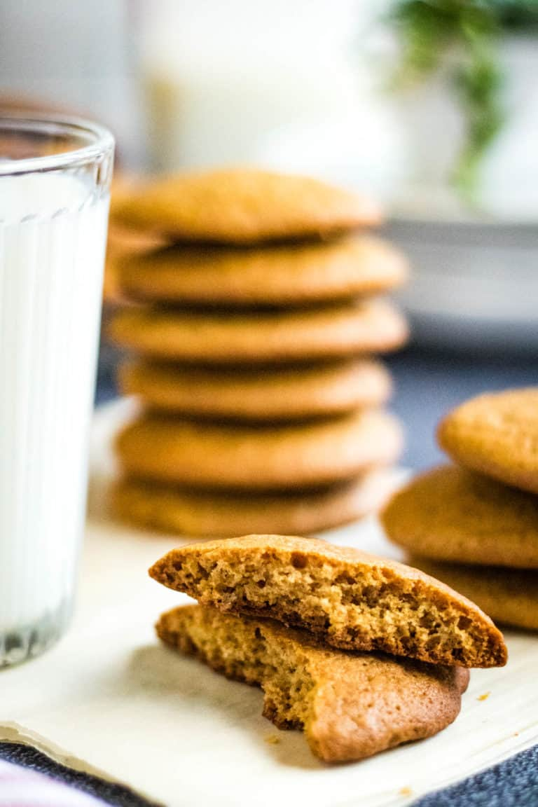 low angle slow-angled shot of a honey cookie broken in half with stacks of honey cookies and a glass of milk in the backgroundhot of a