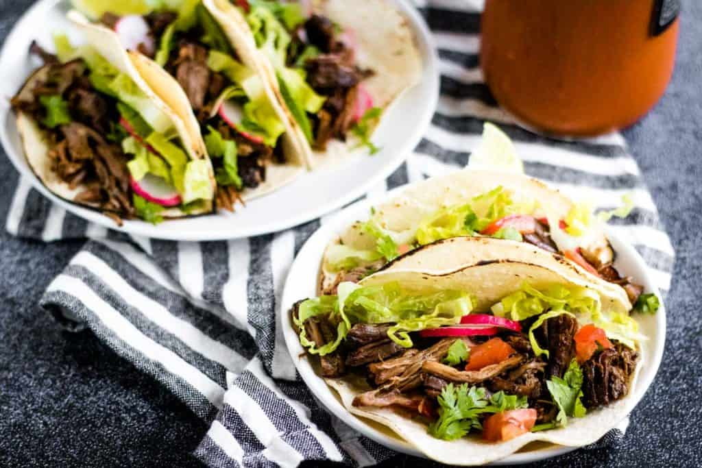Low angle shot of two plates of soft corn tortilla tacos filled with Mexican shredded beef
